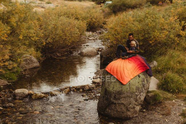 Отец и сын сидят на скале рядом с ручьем, отец учит сына ловить рыбу, минеральный король, Национальный парк Секуа, Калифорния, США — стоковое фото