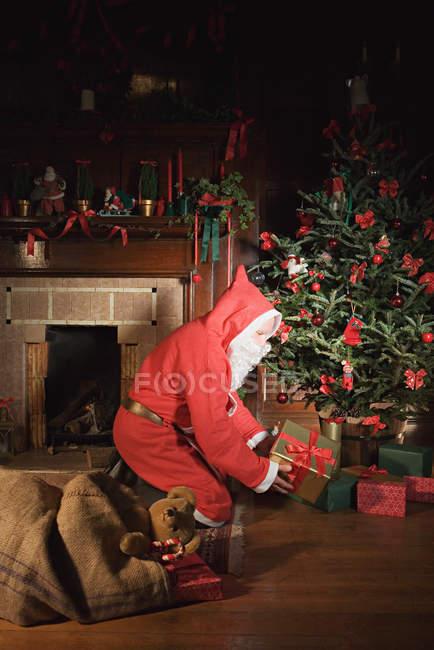 Санта Клаус кладе подарунки під дерево Різдва Христових. — стокове фото
