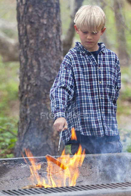Boy barbecuing sausage on flaming grill in forest, Sedona, Arizona, USA — Stock Photo