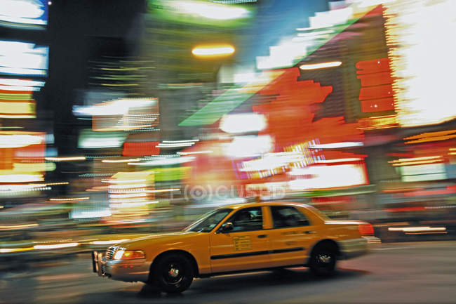 Yellow taxi car and city lights in motion blur — Stock Photo