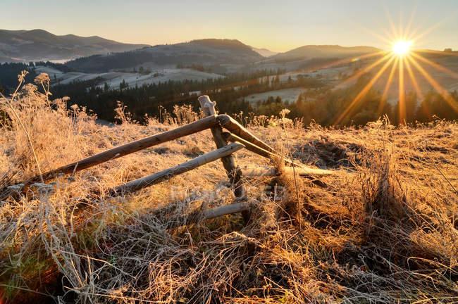 Сломанный забор и восход солнца на морозным утром — стоковое фото