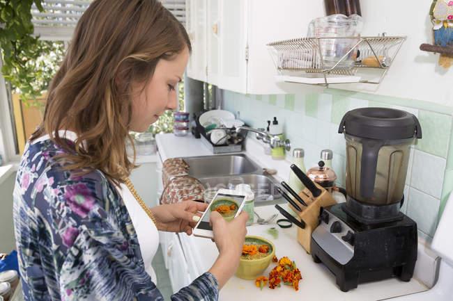 Mujer fotografiando tazón de comida con smartphone - foto de stock