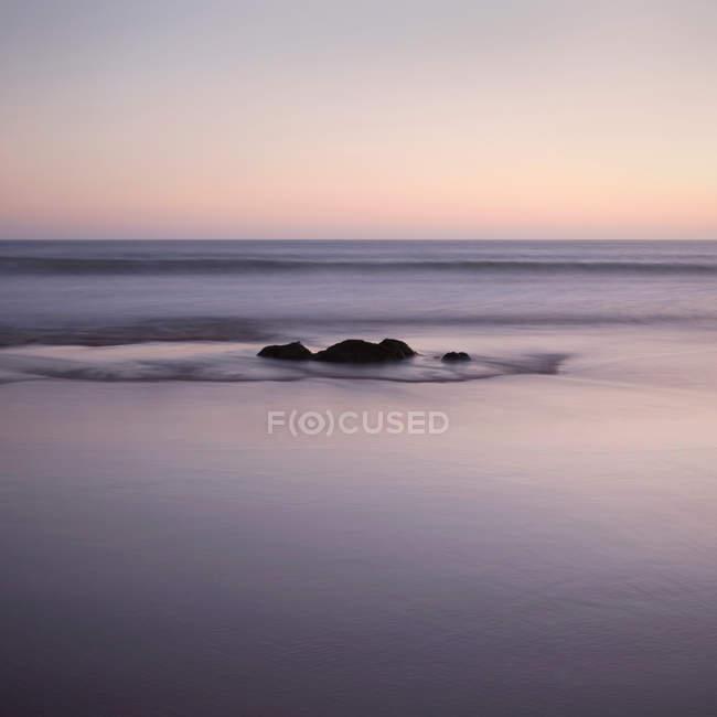 Vista panorâmica da rocha no mar ao pôr-do-sol — Fotografia de Stock
