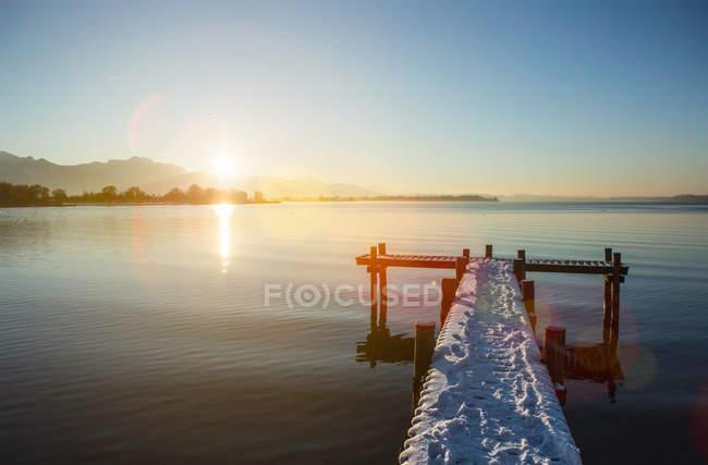Verschneite Pier über See — Stockfoto