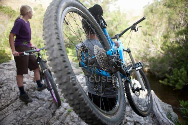 Joven pareja con bicicletas de montaña en roca - foto de stock