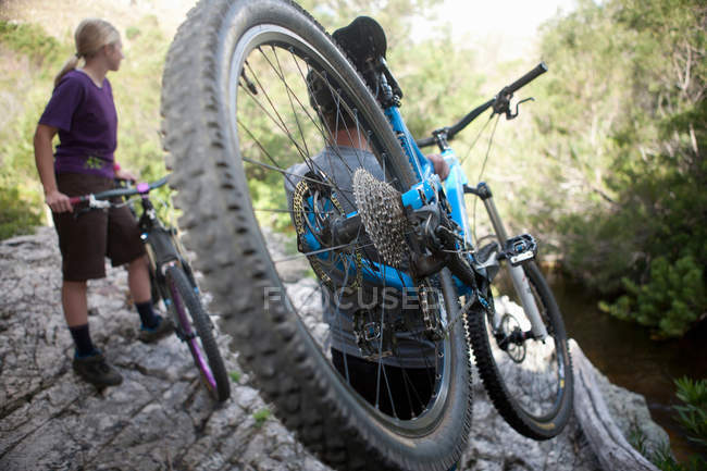 Young couple with mountain bikes on rock — Stock Photo