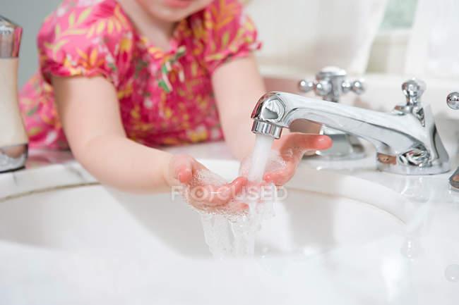 Chica lavándose las manos, imagen recortada - foto de stock
