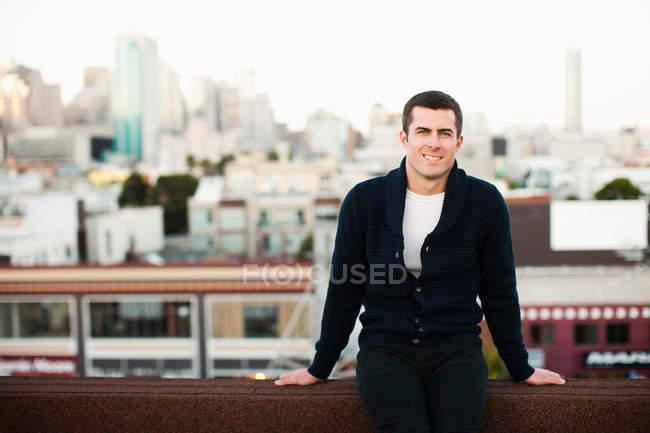 Усміхнений чоловік, сидячи на балконі міської — стокове фото