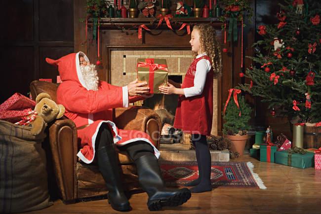 Санта Клаус дарує дівчині подарунок. — стокове фото