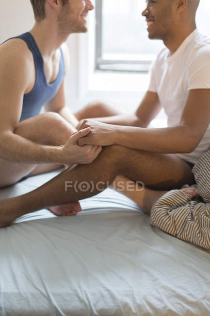 Couple masculin assis sur le lit, face à face, jambes enlacés — Photo de stock