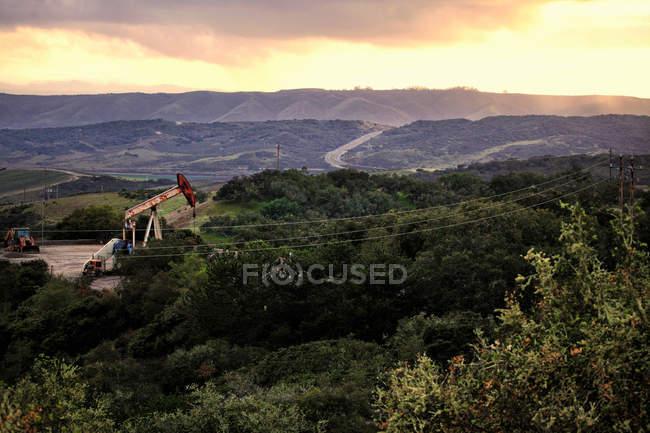 Derricks dans le puits de pétrole dans le paysage rural — Photo de stock