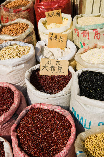 Bags of beans in market stall — Stock Photo