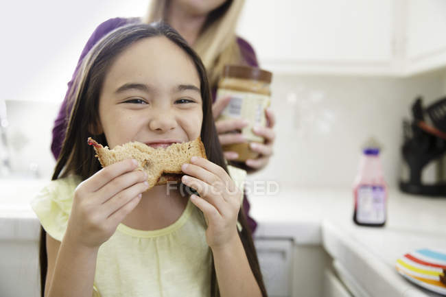 Дівчинка їсть бутерброд і посміхається — стокове фото