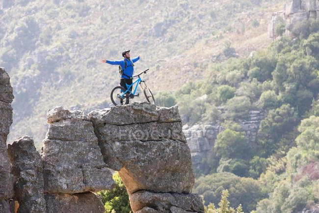 Jeune homme avec VTT et bras tendus sur le rocher — Photo de stock