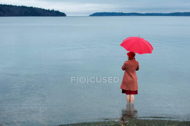 Woman with umbrella in rural lake — Stock Photo