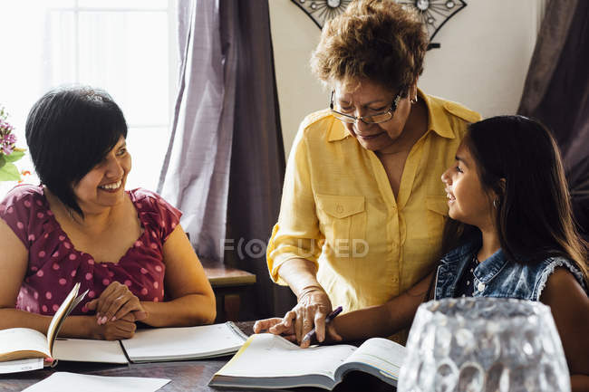 Mother and grandmother helping girl with homework — Stock Photo