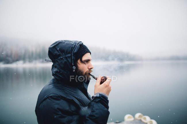 Side view of man smoking pipe by lake, Bass Lake, California, USA — Stock Photo