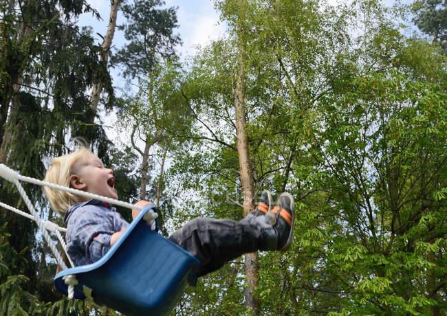 Happy Boy swinging on playground — Stock Photo