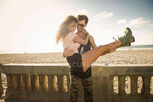 Молодой человек Холдинг подруга оружием на пляже Сан-Диего — стоковое фото