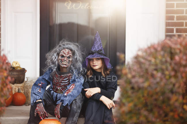 Amis habillés en sorcière et en zombie, assis sur la première marche de la maison — Photo de stock