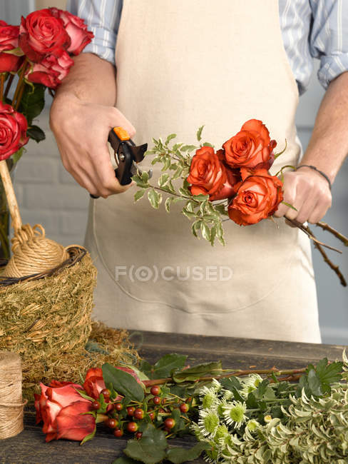 Cropped image of Florist trimming flowers in shop — Stock Photo