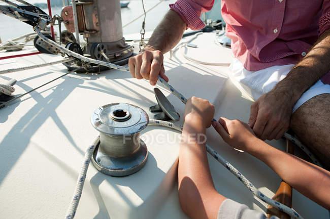 Père et fils à bord du yacht avec corde — Photo de stock
