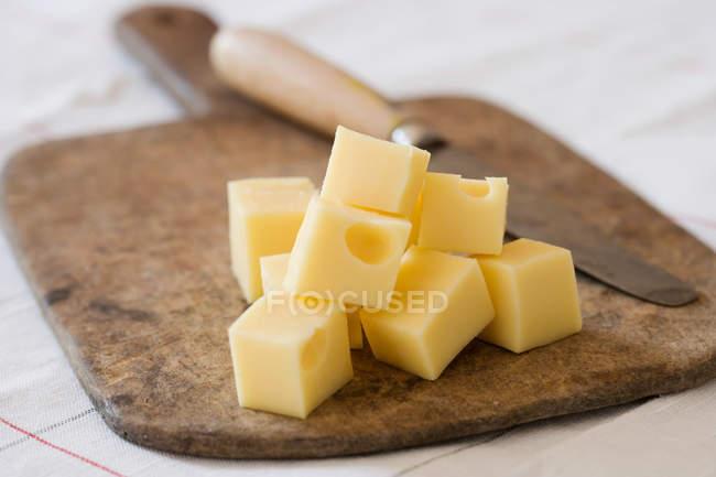 Кубиками сыр с ножом на деревянная разделочная доска — стоковое фото