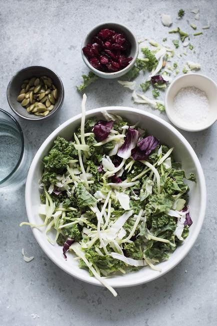 Vue de dessus de la salade de feuilles dans un bol avec accompagnements — Photo de stock