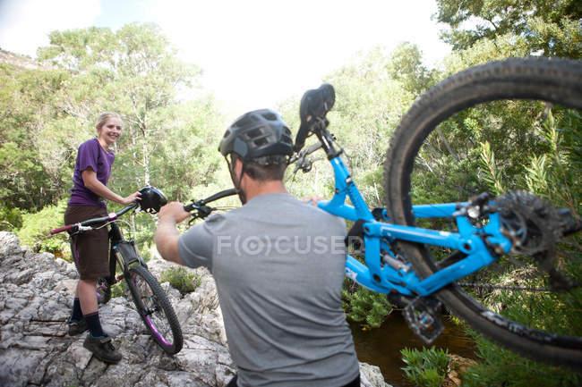Coppia giovane con mountain bike su roccia — Foto stock