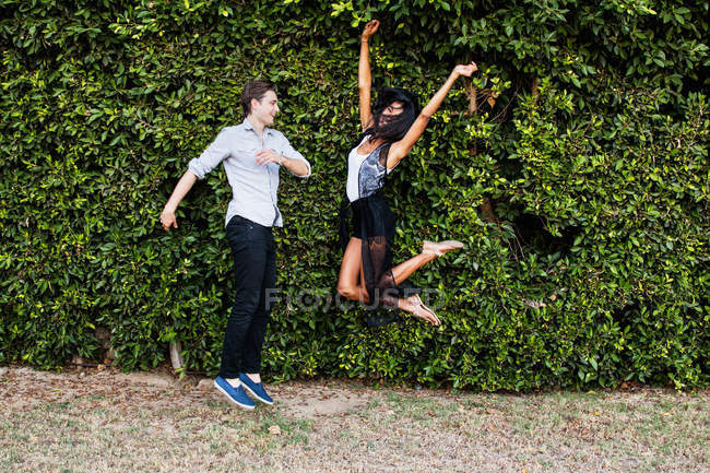 Young couple fooling around outdoors, jumping — Stock Photo