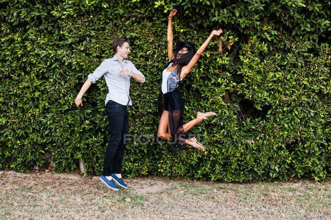 Giovane coppia scherzando all'aperto, saltando — Foto stock
