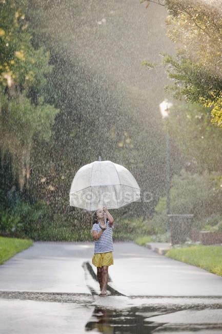 Descalço menina segurando guarda-chuva e andando através de poças na rua — Fotografia de Stock