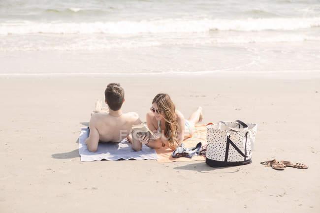 Couple contemporain ayant un bon temps de détente sur la lecture de la plage et au soleil sur des serviettes de plage — Photo de stock