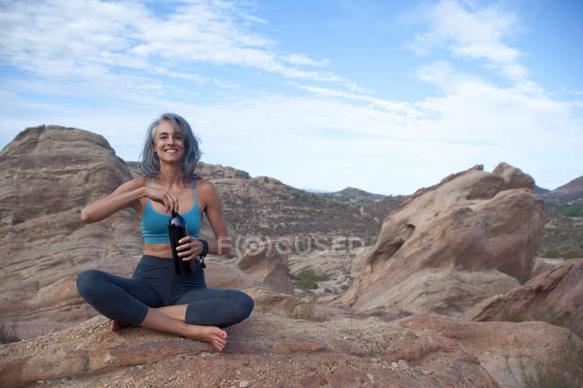 Woman sitting at Vazquez Rocks, opening bottle with drink — Photo de stock
