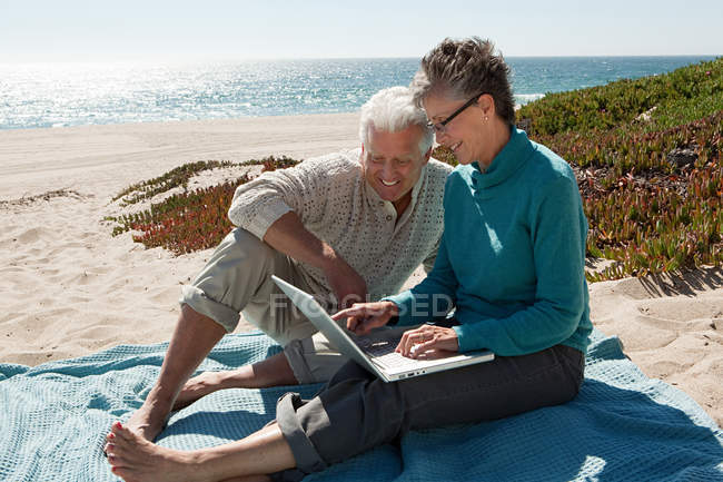 Mature couple using laptop at the beach — Stock Photo