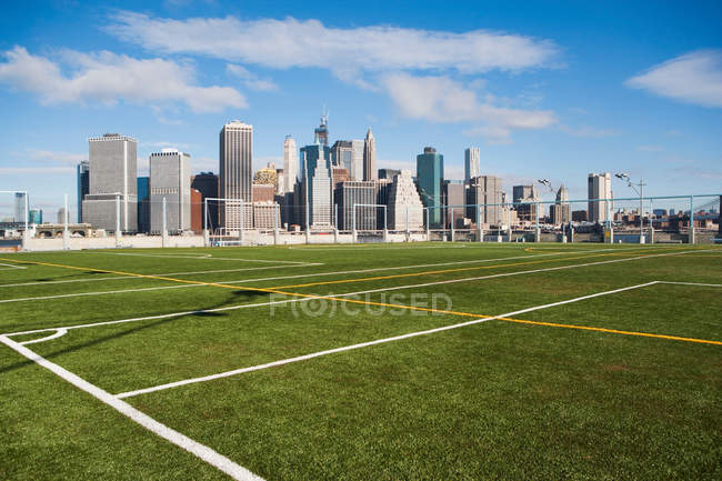 Soccer field and Lower Manhattan skyline in sunlight — Stock Photo
