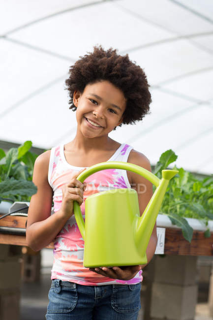 Girl holding green watering can — Stock Photo