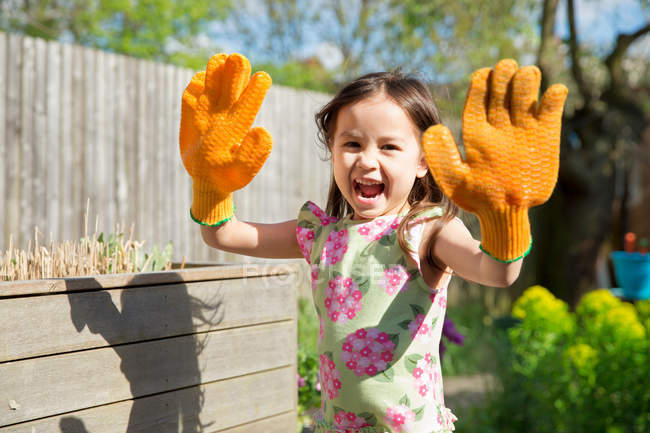 Young girl in garden wearing oversized gloves — Stock Photo