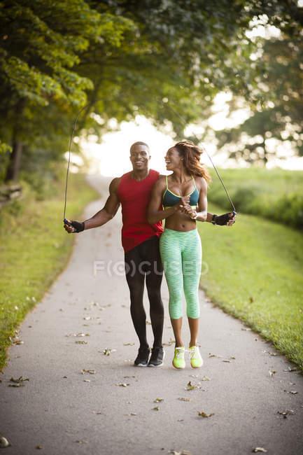Jovens casais treinando no caminho pulando na unidade — Fotografia de Stock