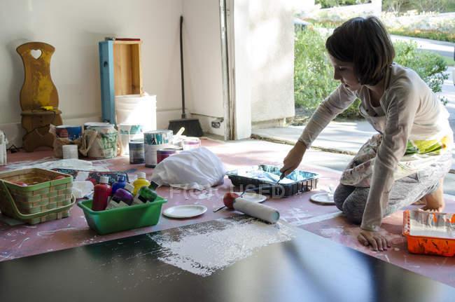 Mädchen in Garagenmalerei mit Farbroller — Stockfoto