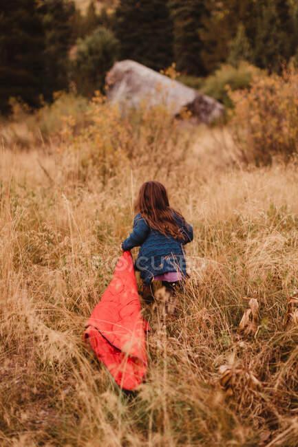 Junges Mädchen läuft durch langes Gras, schleppt Schlafsack, Rückansicht, Mineral King, Sequoia National Park, Kalifornien, USA — Stockfoto