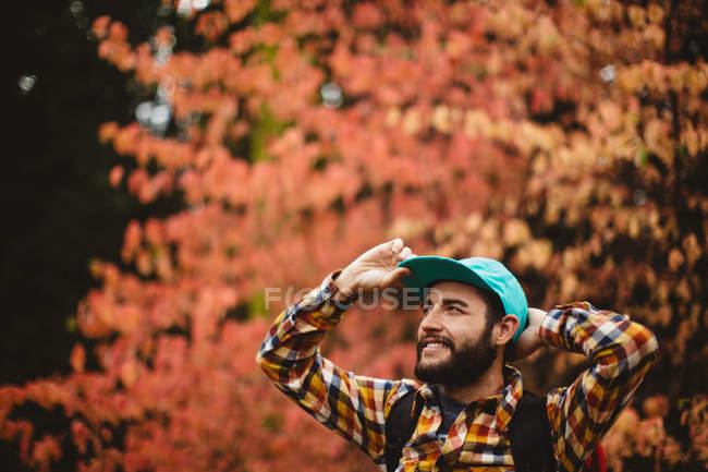 Junger Mann in ländlicher Umgebung, mit Baseballmütze, lächelnd — Stockfoto