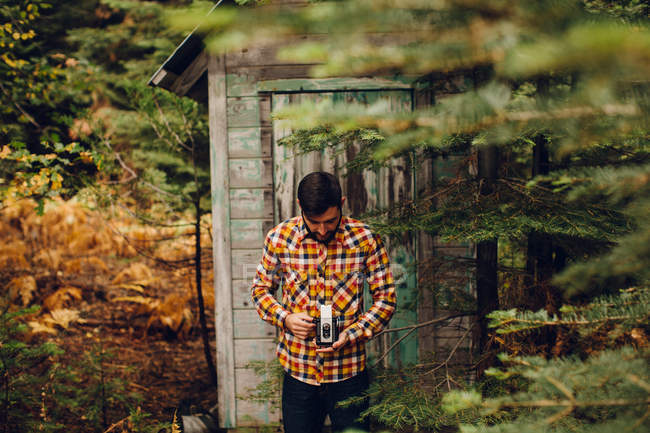 Junger Mann steht in der Nähe von Hütte im Wald, Fotografieren mit Kamera, in der Nähe von Rasierer See, Kalifornien, USA — Stockfoto