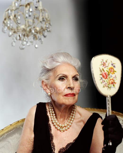 Seniorin sieht sich im Handspiegel an — Stockfoto