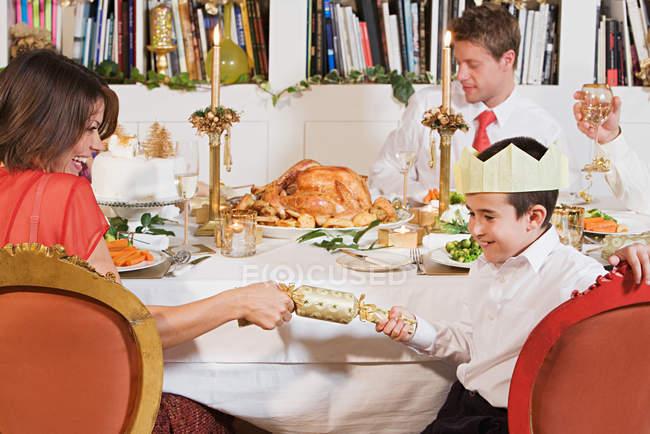 Famiglia tirando cracker di Natale — Foto stock