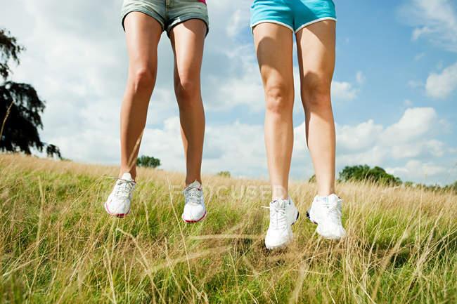 Jeunes filles sautant dans un champ — Photo de stock