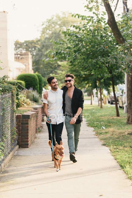 Young male couple walking with dog on suburban sidewalk — Stock Photo