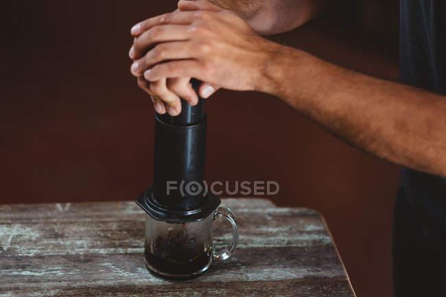 Man using aeropress coffee maker — Stock Photo