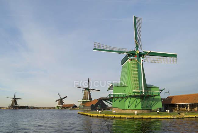 Fila de molinos de viento contra el cielo nublado en Zaanse Schans, Zaandam, Países Bajos - foto de stock