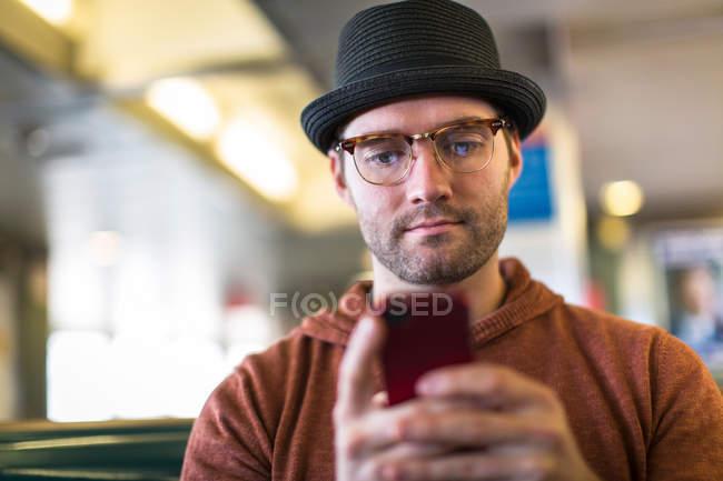 Uomo che per mezzo del telefono cellulare sul banco — Foto stock